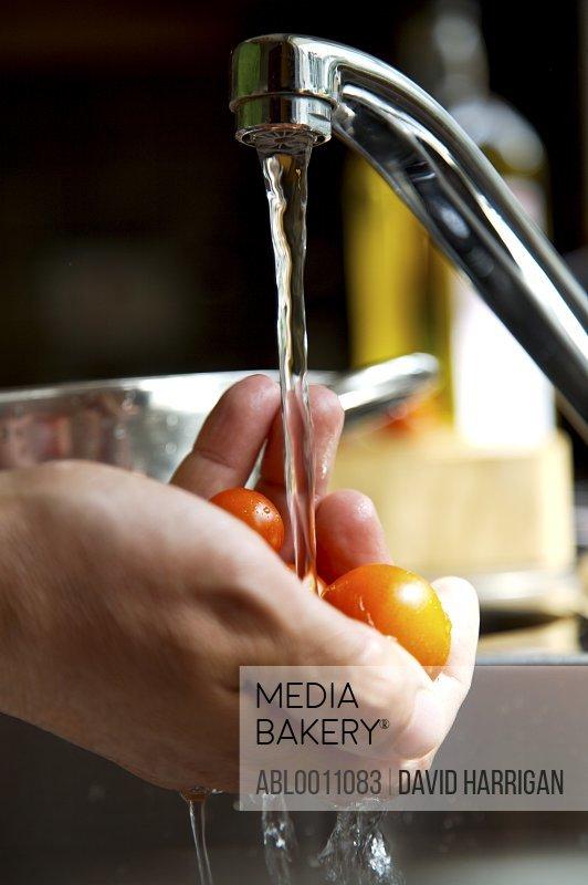 Man's hands washing cherry tomatoes with running water