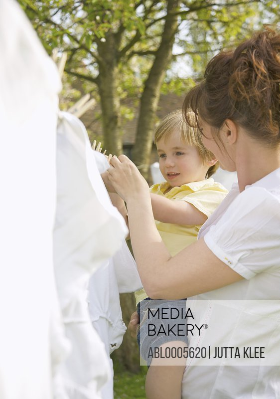 Young boy helping mother hanging linens on a clothesline