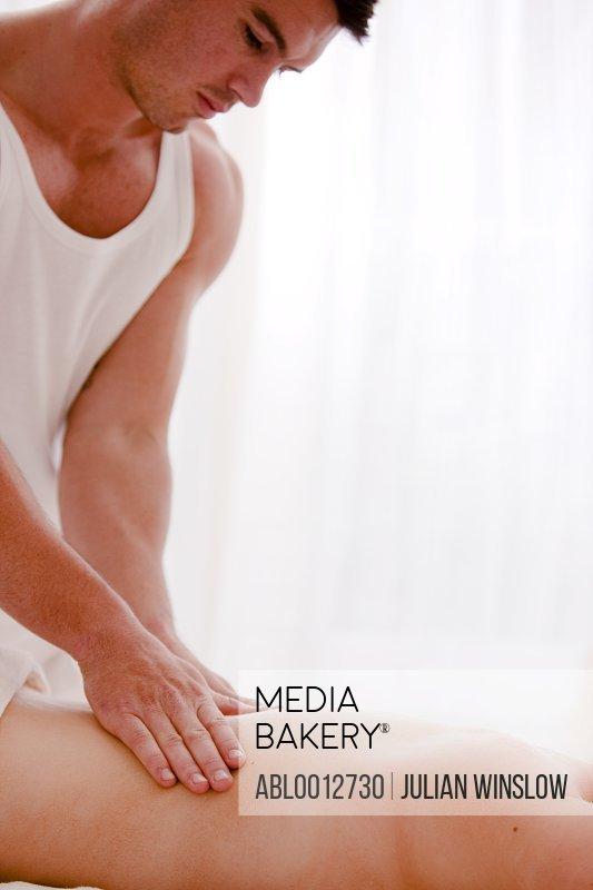 Masseur giving a woman a back massage
