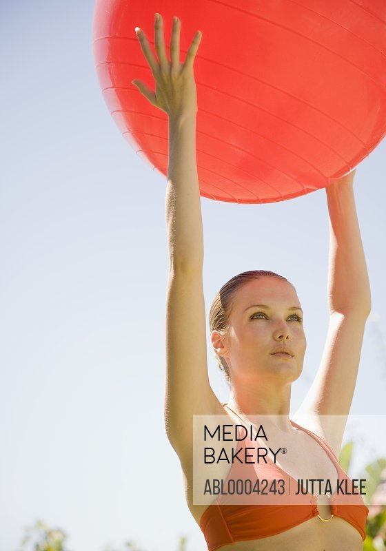 Young Woman Holding Red Exercise Ball