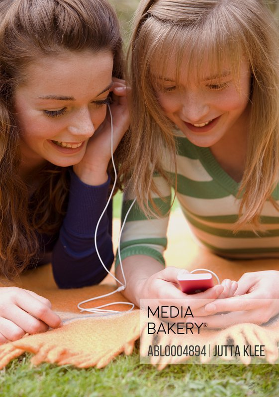 Two smiling teenaged girls lying on a blanket holding and mp3 player and listening to music