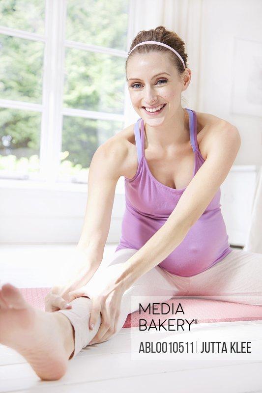 Smiling Pregnant Woman Practicing Yoga