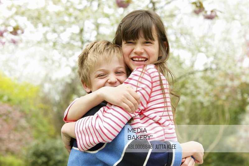 Smiling Boy and Girl Hugging Outdoors
