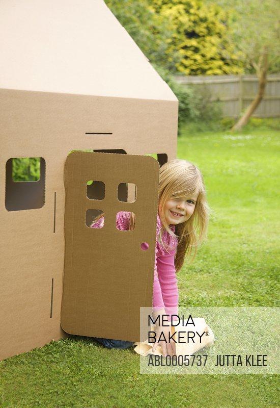 Smiling young girl kneeling in the doorway of a cardboard playhouse