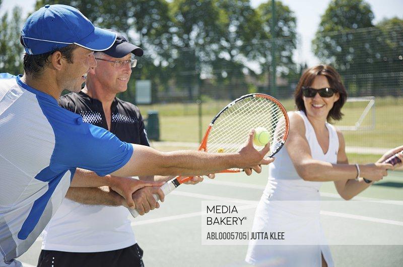 Tennis teacher instructing a couple