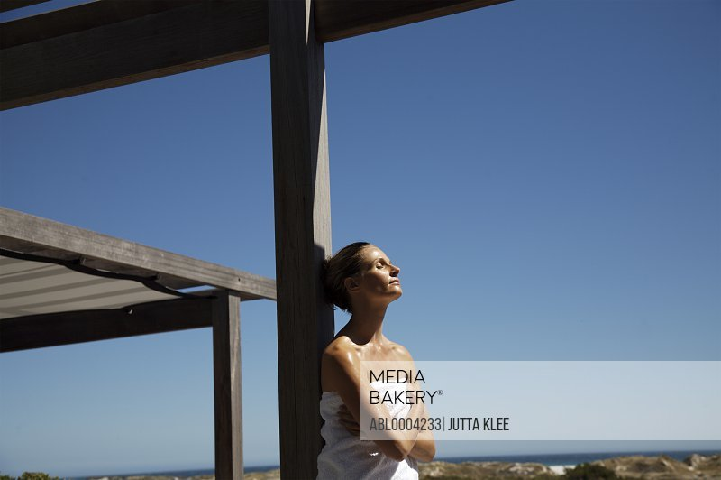 Woman wearing towel leaning against wooden beam relaxing