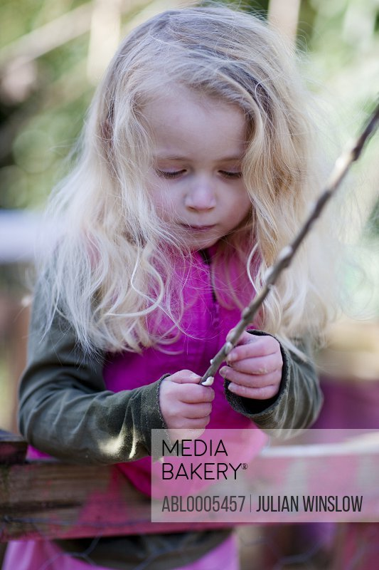 Girl holding  and inspecting a stick