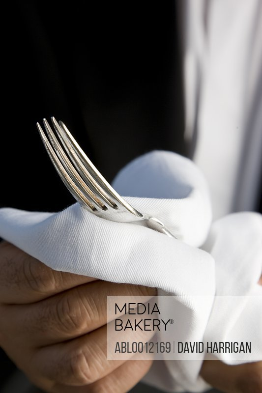 Close up of a waiter hands polishing a silver fork with a white napkin