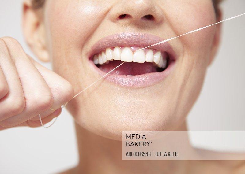 Woman Flossing Teeth - Close-up view
