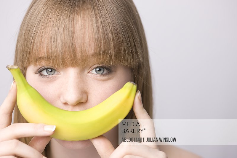 Close up of young woman covering mouth with banana