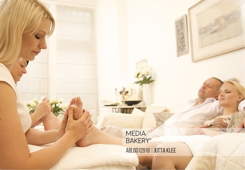 Couple at home receiving a foot massage