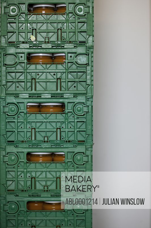 Close up of a stack of green plastic crates filled with glass jars