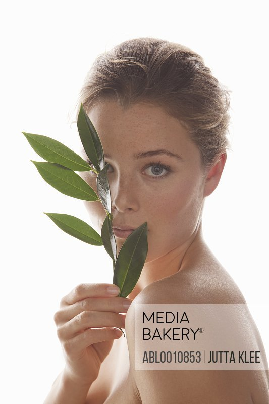 Woman Holding Green Leafed Twig in front of her Face