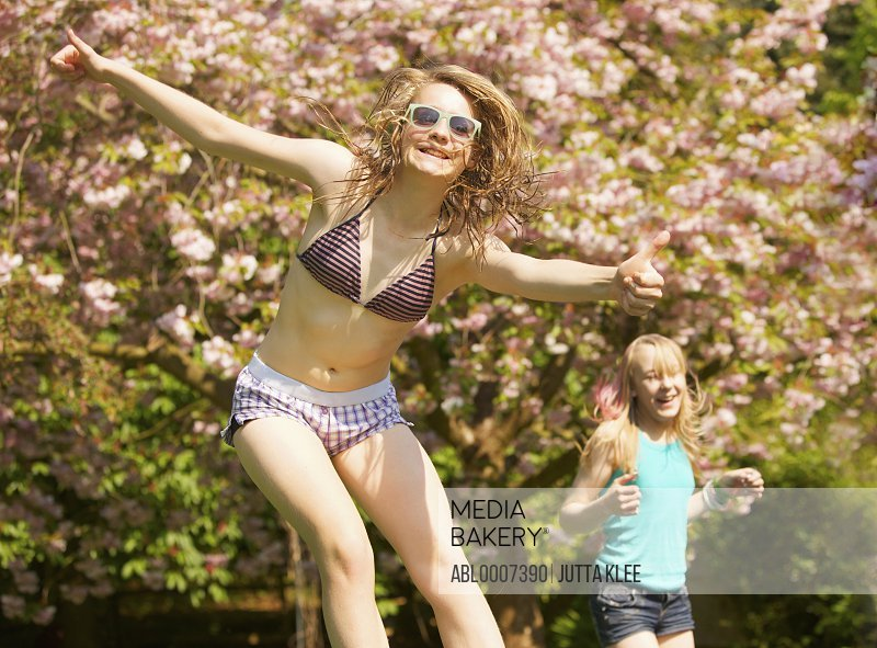 Teenage Girls Bouncing on Trampoline in front of Blooming Tree