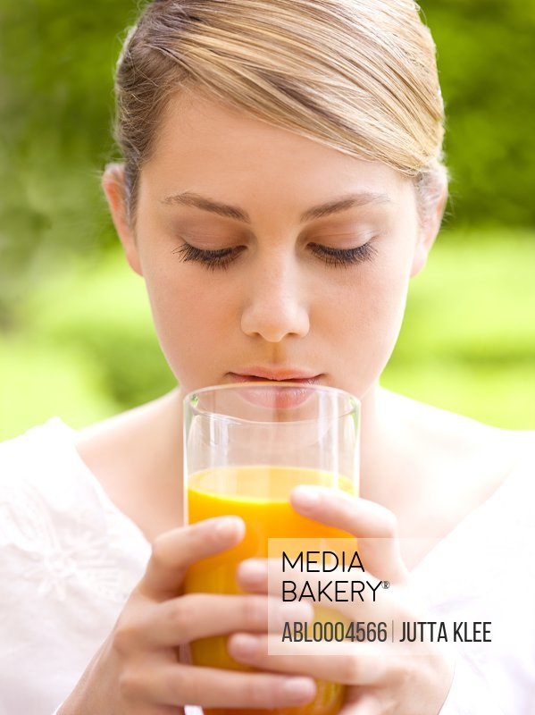 Close up of a young woman holding a glass of orange juice