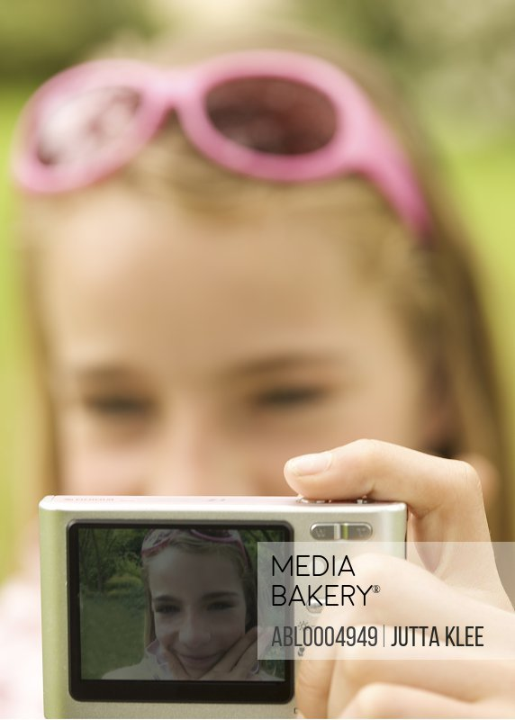Close up of a girl holding a digital camera and taking a self-portrait