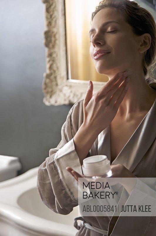 Woman applying cream on her neck