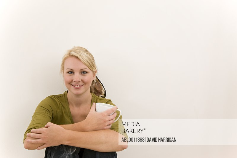 Smiling woman sitting against white wall with arms around knees holding a coffee cup