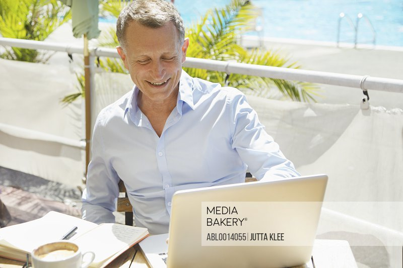 Mature Man Using Laptop at Outdoors Cafe Smiling