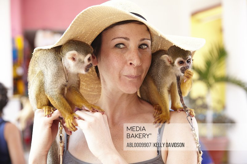 Woman with Spider Monkeys on her Shoulders Making Faces