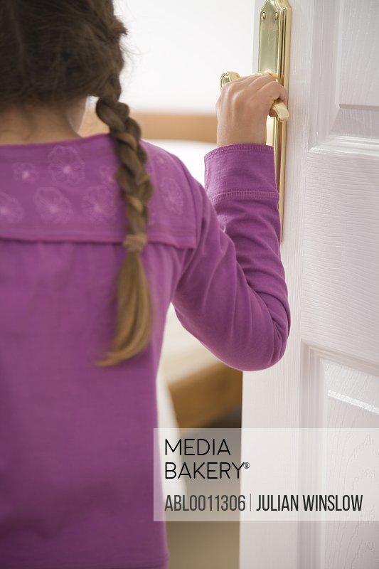 Back view of girl opening bedroom door