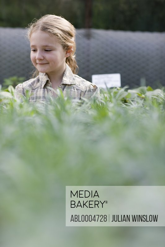 Young girl in a nursery looking at plants smiling