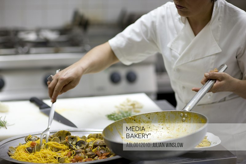Woman chef holding a frying pan and preparing seafood pasta for service