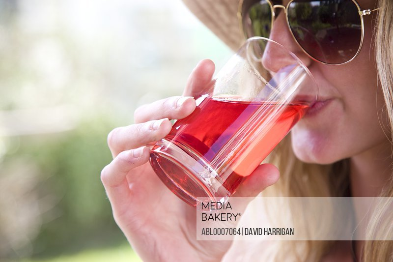 Woman Wearing Aviators Drinking Cranberry Juice