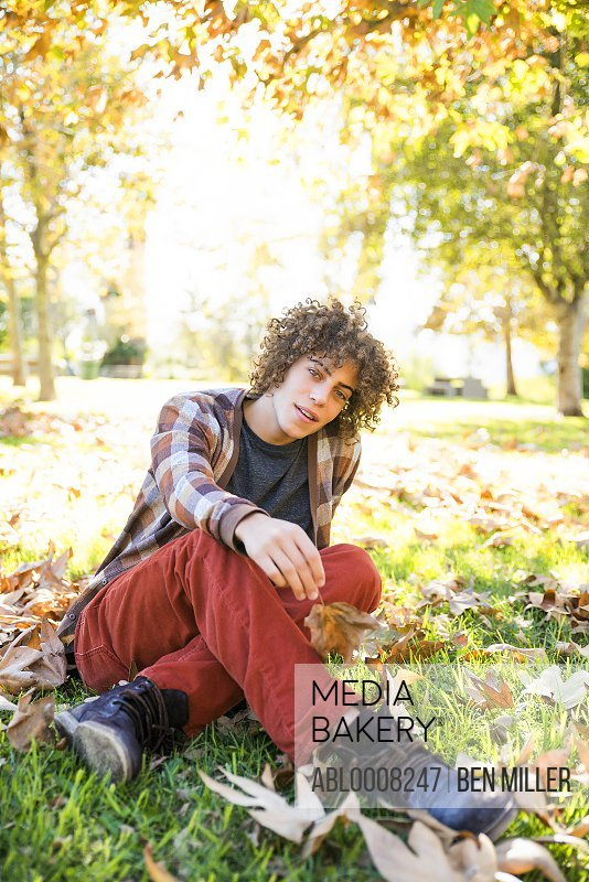 Young Man Sitting in Park in Autumn