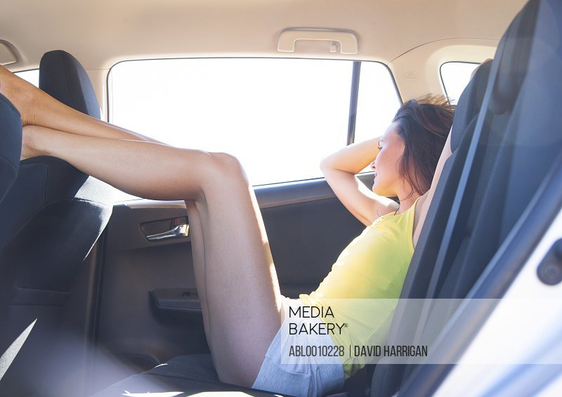 Woman Reclining in Car Back Seat with Legs Raised