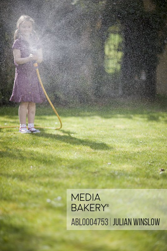 Young girl spraying the lawn with garden hose