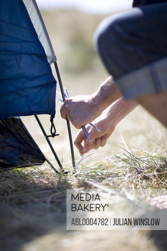 Camper hands fixing tent pole