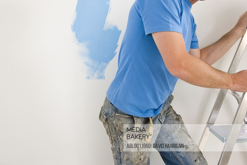 Man decorating going up a ladder with jeans covered in paint