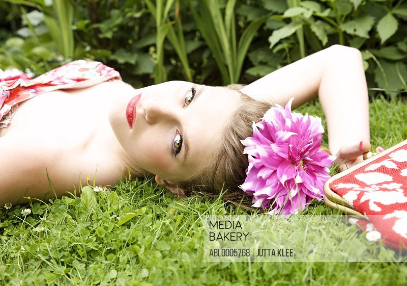 Close up of a young woman lying on the grass with a flower in her hair