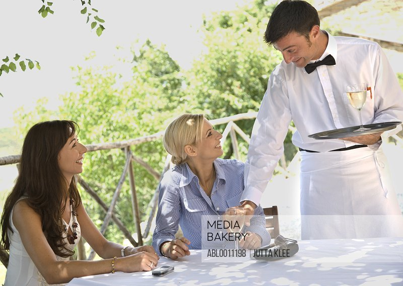 Waiter holding tray serving white wine to women sitting at restaurant table