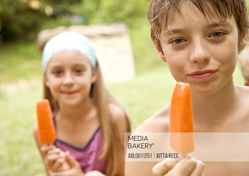 Young Boy and young girl eating orange ice-lolly