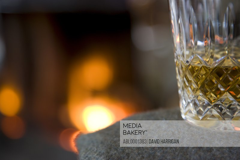 Close up of a glass of whiskey in front of a fireplace