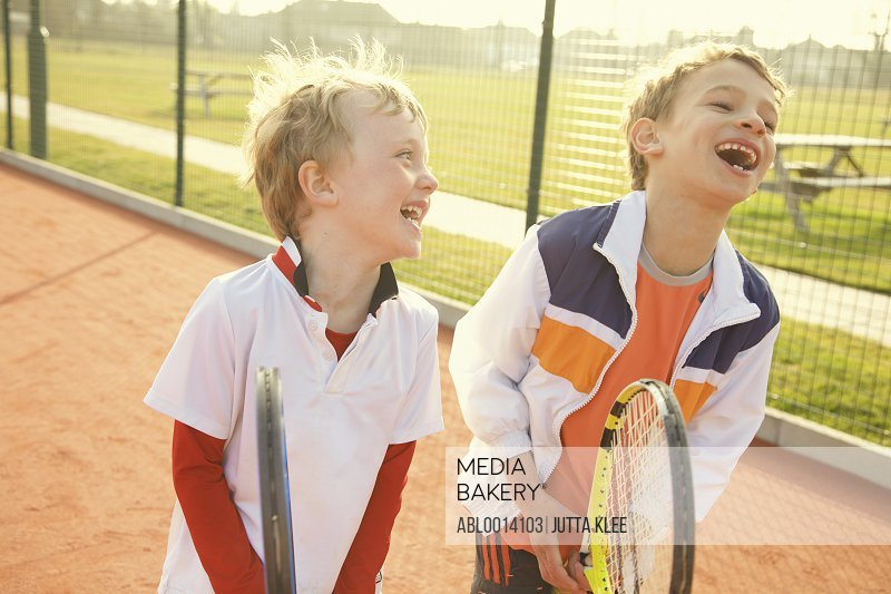 Two Young Boys Holding Tennis Rackets Smiling