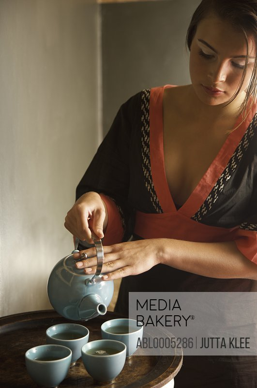 Young woman holding teapot and pouring green tea