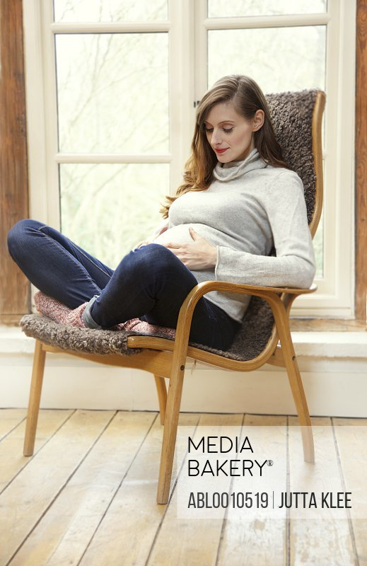 Pregnant Woman Sitting on Armchair Holding her Stomach