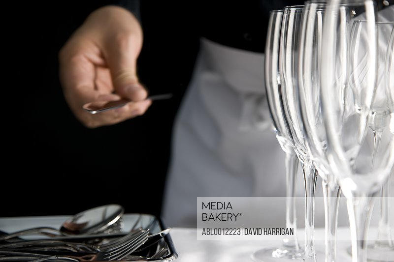Close up of a waiter hand organizing cutlery and glasses