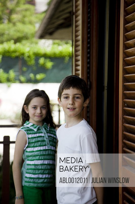 Young boy and young girl standing by window with wooden shutters