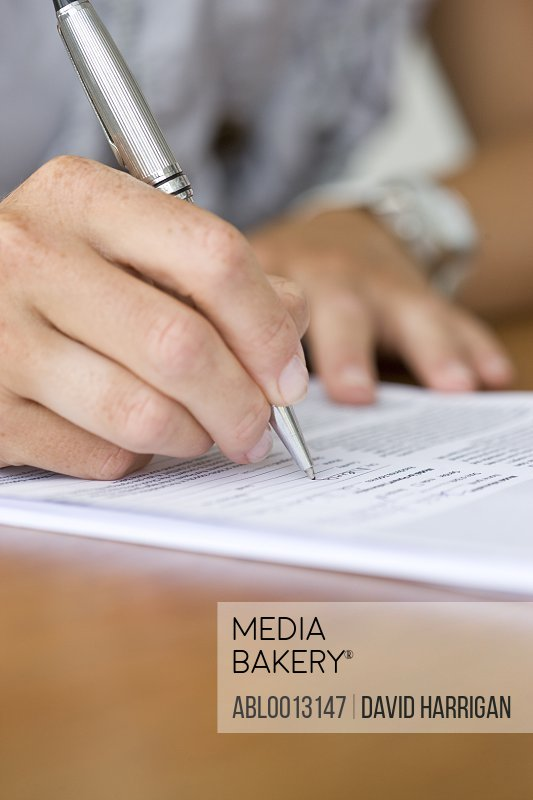 Close up of Woman's Hand Signing Paperwork