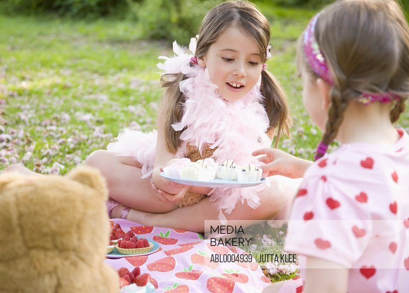 Young girl sitting in pink feather boa offering cupcakes to a friend