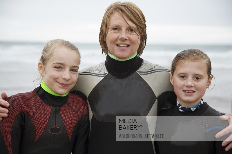 Woman and two girls wearing surfing wetsuits standing on a beach smiling