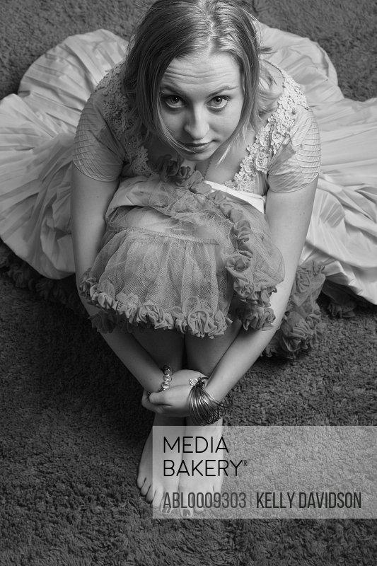 Woman Sitting on Floor Hugging Knees