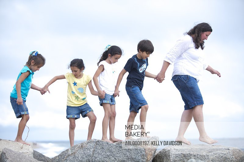 Family Walking on Rocks by Sea Holding Hands