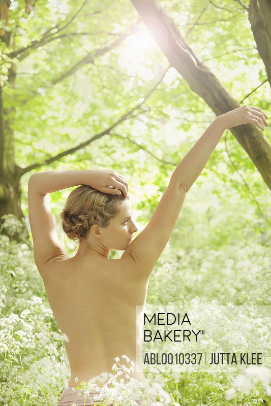Back View of Nude Woman with Arms Raised In a Meadow