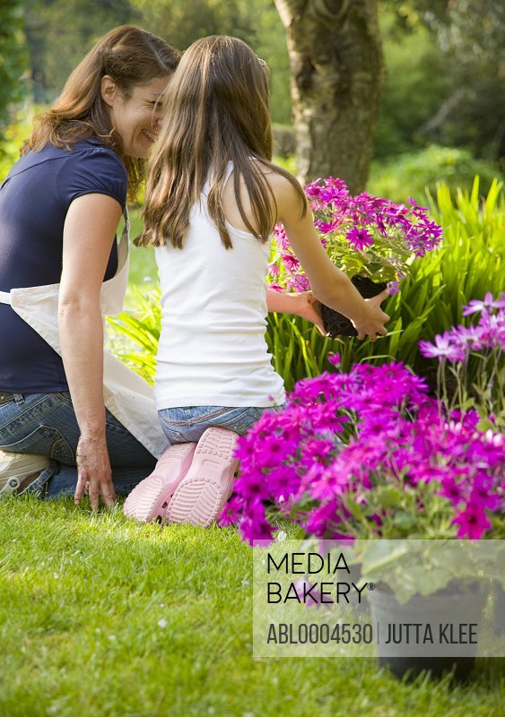 Back of mother and daughter kneeling in the garden tending plants and smiling
