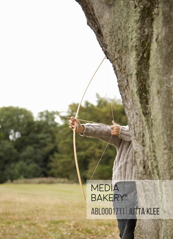 Young boy partially hidden by a tree aiming with a bow and arrow